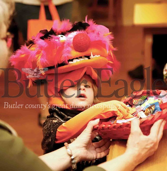Dressed in a homemade Animal costume from the Muppets, Luckas Morris, 2, reaches into a candy basket  in one of the community neighborhood rooms at the New Haven Court at Clearview retirement home. Costume-clad kids crowded the halls  and made their rounds in the senior community trick-or-treating with residents Tuesday evening. Seb Foltz/Butler Eagle