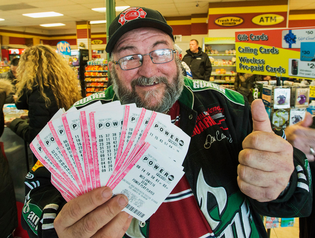. Robert Charbonneau, from Saint-Donat, Quebec, holds up $1,000 worth of Powerball tickets for himself and his friends at a convenience store in the border town of Champlain, N.Y., Tuesday, Jan. 12, 2016. The jackpot lottery has reached a record setting of more than $1 billion. (Ryan Remiorz/The Canadian Press via AP)