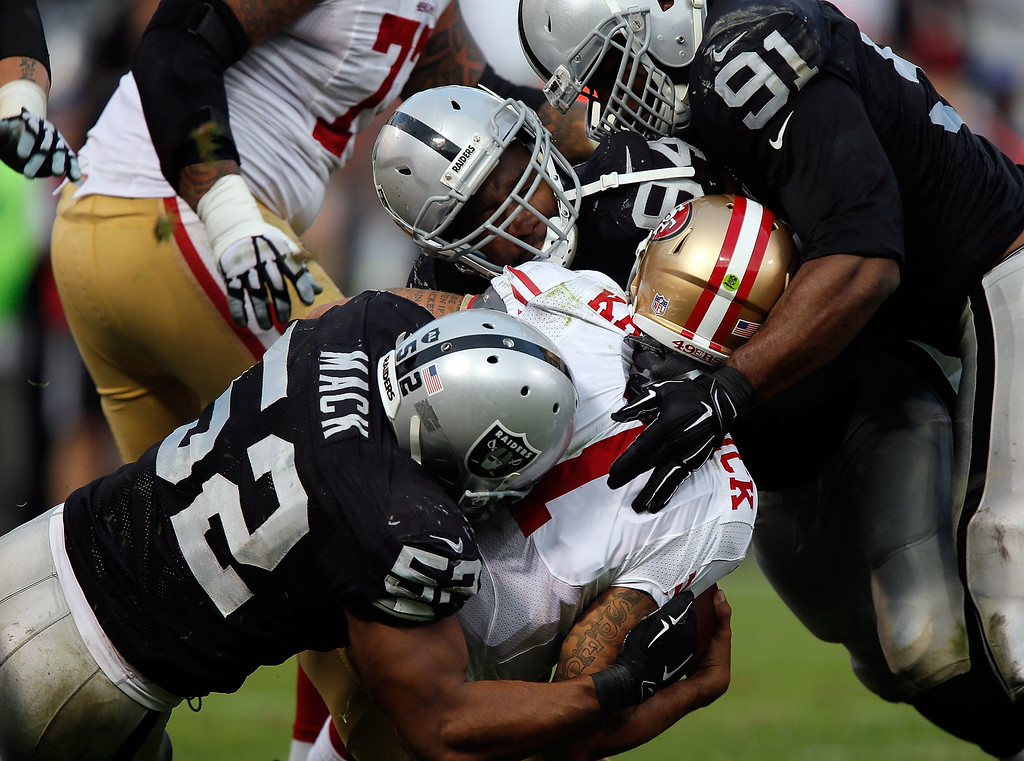 . OAKLAND, CA - DECEMBER 07:  Justin Tuck #91 of the Oakland Raiders, Antonio Smith #94 of the Oakland Raiders, Khalil Mack #52 of the Oakland Raiders sack Colin Kaepernick #7 of the San Francisco 49ers in the fourth quarter at O.co Coliseum on December 7, 2014 in Oakland, California.  (Photo by Brian Bahr/Getty Images)