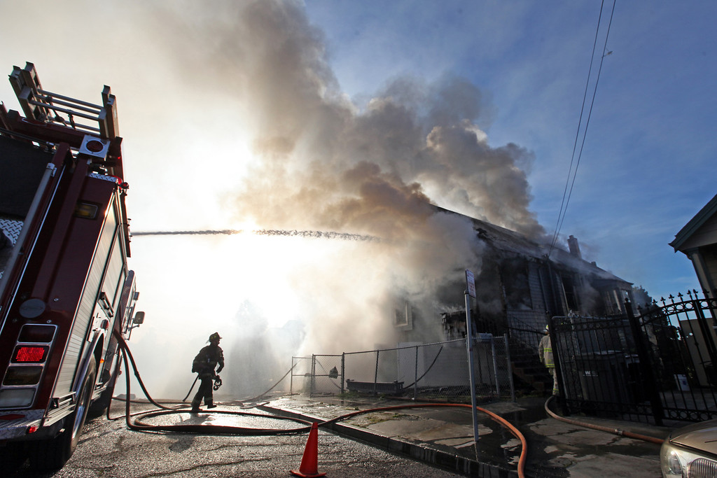 . Oakland firefighters battle a fully involved house fire at a three-story wood-frame house in the 2000 block of East 26th Street in Oakland, Calif., on Tuesday, Jan. 15, 2013.  The owner was not home when the fire started, said Battalion Chief Jenny Ray. (Laura A. Oda/Staff)