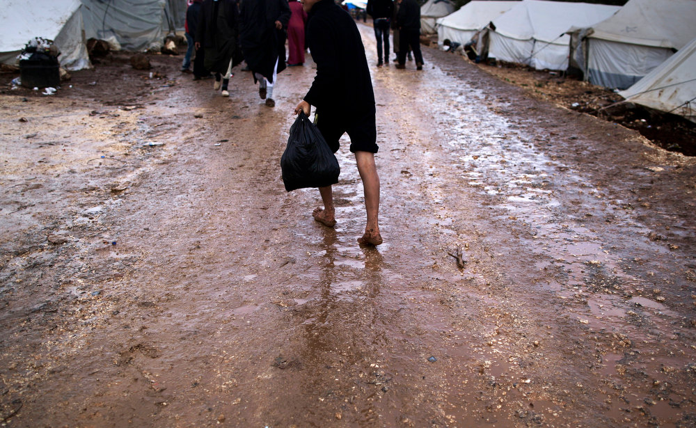 Description of . A Syrian boy who fled his home walks barefoot on a muddy path back to his tent, at a camp for displaced Syrians, in the village of Atmeh, Syria, Tuesday, Dec. 11, 2012. This tent camp sheltering some of the hundreds of thousands of Syrians uprooted by the country's brutal civil war has lost the race against winter: the ground under white tents is soaked in mud, rain water seeps into thin mattresses and volunteer doctors routinely run out of medicine for coughing, runny-nosed children. (AP Photo/Muhammed Muheisen)