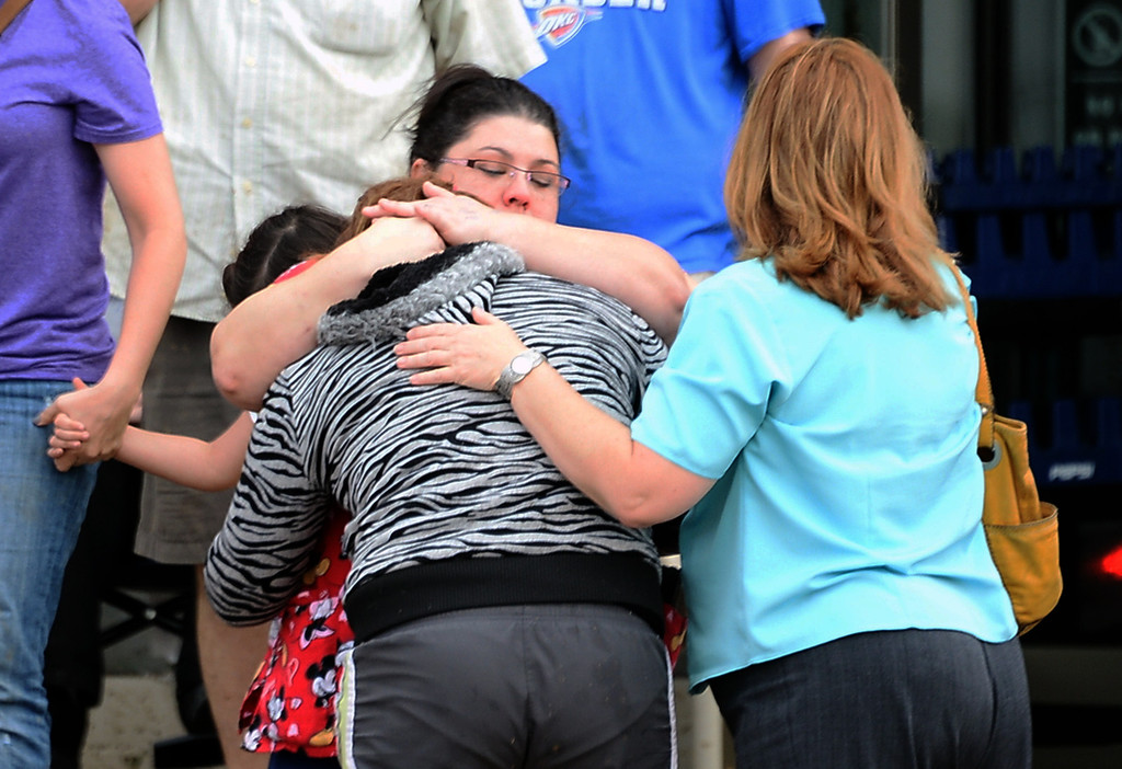 . A woman is given comfort by friends after a tornado destroyed buildings and overturned cars in Morre, Oklahoma.