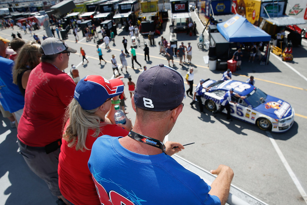 . DAYTONA BEACH, FL - JULY 06:  Fans watch crew members push the #55 Aaron\'s Dream Machine Toyota driven by Michael Waltrip (not pictured) through the garage area during the NASCAR Sprint Cup Series Coke Zero 400 at Daytona International Speedway on July 6, 2013 in Daytona Beach, Florida.  (Photo by Scott Halleran/Getty Images)