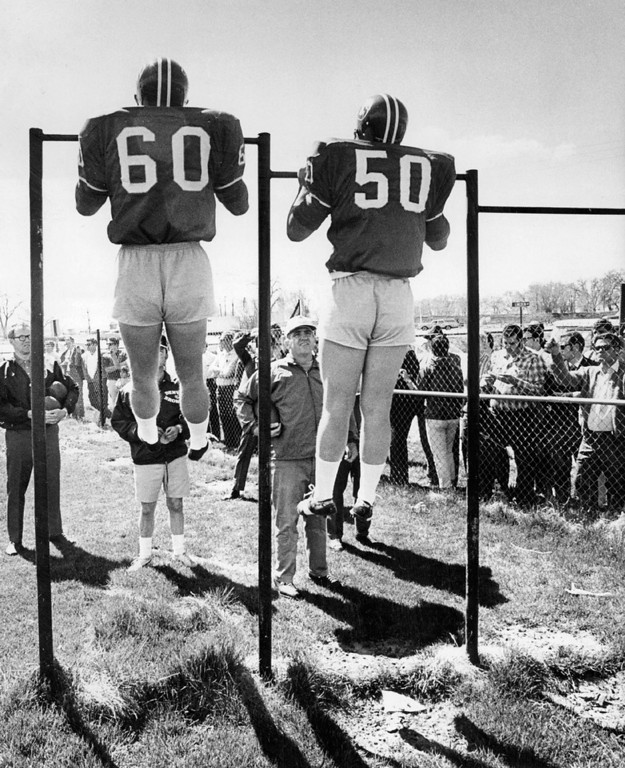 . May 8, 1970: Linebackers Bill Butler, left, of San Fernando State and Mike Kennedy of Arizona State did pull-ups in some very short shorts as coaches watched. (Bill Wunsch, The Denver Post)