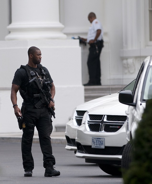""". A member of the US Secret Service stands guard on the North Lawn of the White House in Washington, DC, October 3, 2013, following reports of a shooting at the US Capitol.  \""""We heard what was about four shots,\"""" said Senator Bernie Sanders as tourists and lawmakers rushed into the building to take cover and police hurried to secure the area. Emergency vehicles converged on the scene, focused on the north side of the iconic landmark, where an AFP photographer saw visitors scattering and ducking for cover. AFP PHOTO / Saul LOEB/AFP/Getty Images"""