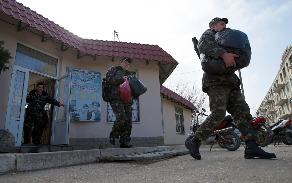 . Ukrainian air force officers walk with their bags at the Belbek airbase, outside Sevastopol, Crimea, on Thursday, March 20, 2014. With thousands of Ukrainian soldiers and sailors trapped on military bases, surrounded by heavily armed Russian forces and pro-Russia militia, the Kiev government said it was drawing up plans to evacuate its outnumbered troops from Crimea back to the mainland and would seek U.N. support to turn the peninsula into a demilitarized zone. (AP Photo/Ivan Sekretarev)