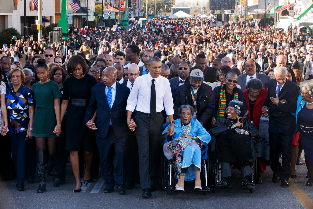 ". ADDS NAME OF SECOND WOMAN IN WHEELCHAIR - President Barack Obama, center, walks as he holds hands with Amelia Boynton Robinson, who was beaten during ""Bloody Sunday,\"" as they and the first family and others including Rep. John Lewis, D-Ga,, left of Obama, walk across the Edmund Pettus Bridge in Selma, Ala. for the 50th anniversary of ìBloody Sunday,\"" a landmark event of the civil rights movement, Saturday, March 7, 2015. From front left are Marian Robinson, Sasha Obama. first lady Michelle Obama. Obama, Robinson and Adelaide Sanford, also in wheelchair. (AP Photo/Jacquelyn Martin)"