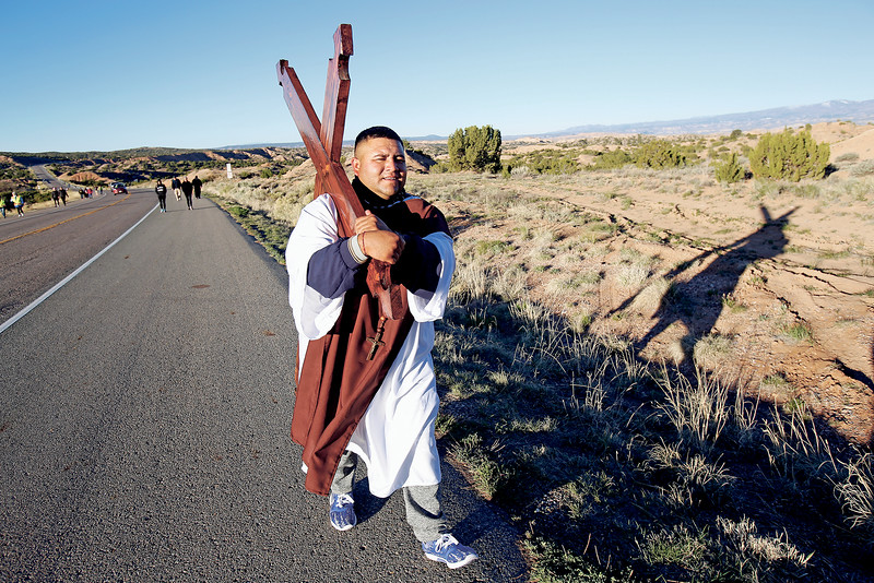 Juan Campos of Lovington, NM, carries a cross for a friend's mother who passed away during his pilgrimage to the Santuario de Chimayo on Good Friday, April 19, 2019. This is Campos' 20th year doing the pilgrimage but only his first year carrying the cross. Luis Sánchez Saturno/The New Mexican