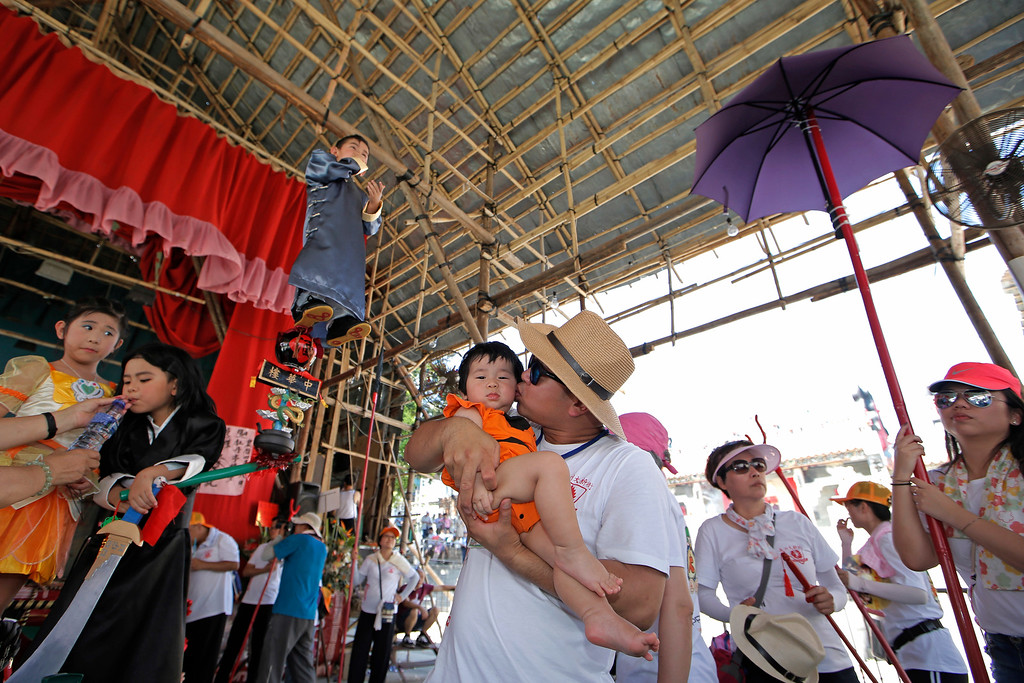 . A man kisses his son as a child dressed in a traditional Chinese costume floats in the air, supported by a rig of hidden metal rods, during a parade on the outlying Cheung Chau island in Hong Kong to celebrate the Bun Festival Tuesday, May 22, 2018. Bun Festival, the Taoist God of the Sea, is worshipped and evil spirits are scare away by loud gongs and drums during the procession. The celebration includes bun scrambling, parades, opera performances, and children dressed in colorful costumes. (AP Photo/Kin Cheung)