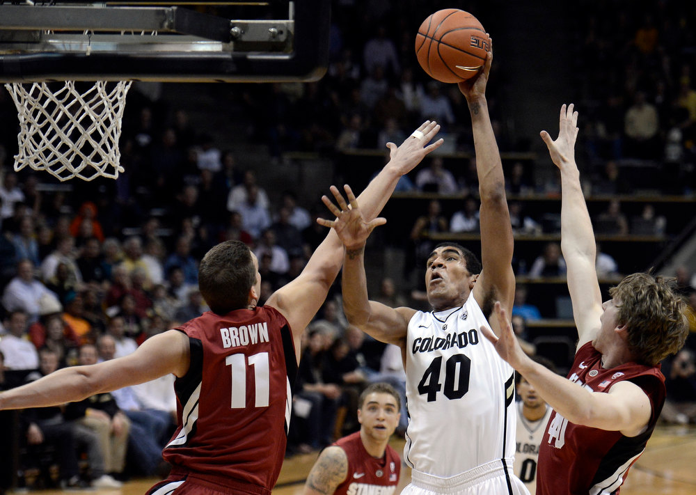 . University of Colorado\'s Josh Scott takes a shot over Robbie Lemons, No. 11, and John Gage, at right, during a game against Stanford on Thursday, Jan. 24, at the Coors Event Center on the CU campus in Boulder. Jeremy Papasso/ Camera