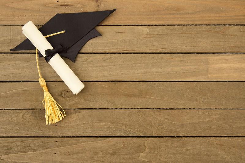 Symbols Representing Graduation on a Wooden Table