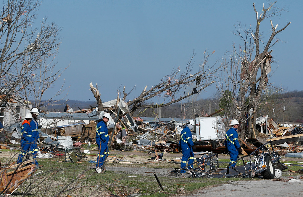 . Oklahoma Natural Gas workers walk through the tornado-damaged River Oaks Estates mobile home park in Sand Springs, Okla.,, Thursday, March 26, 2015. Gov. Mary Fallin has declared a state of emergency for 25 Oklahoma counties after powerful storms rumbled across the state Wednesday evening and produced tornadoes and flat-line winds that led to one death, numerous injuries and widespread damage. (AP Photo/Sue Ogrocki)