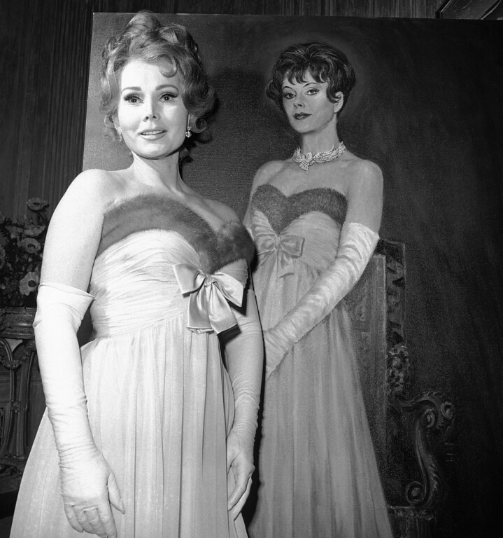 ". Actress Zsa Gabor, who has been named to replace Hedy Lamarr in the movie, ""Picture Mommy Dead,\""  poses  Feb. 4, 1966  with a painting of Hedy  done especially the picture.   Zsa  Zsa wears the same mink and chiffon gown in the painting at Hollywood studio in Los Angels, Calif.    (AP Photo)"