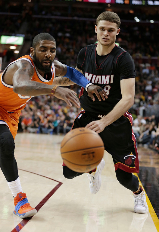 . Cleveland Cavaliers\' Kyrie Irving, left, and Miami Heat\'s Tyler Johnson battle for a loose ball in the second half of an NBA basketball game Friday, Dec. 9, 2016, in Cleveland. The Cavaliers won 114-84. (AP Photo/Tony Dejak)