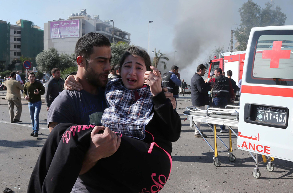 . A Lebanese man carries an injured girl following a bomb explosion in a southern suburb of the capital Beirut on February 19, 2014.  AFP PHOTO / STR-/AFP/Getty Images