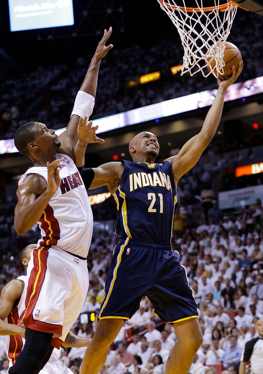 . Indiana Pacers forward David West (21) drives to the basket over Miami Heat center Chris Bosh (1) during the first half of Game 4 in the NBA basketball Eastern Conference finals playoff series, Monday, May 26, 2014, in Miami. (AP Photo/Wilfredo Lee)