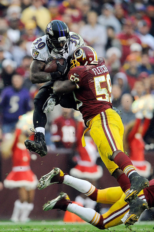 . LANDOVER, MD - DECEMBER 09:  Bernard Pierce #30 of the Baltimore Ravens leaps to avoid the tackle of DeAngelo Hall #23 and London Fletcher #59 of the Washington Redskins during a game at FedExField on December 9, 2012 in Landover, Maryland.  (Photo by Patrick McDermott/Getty Images)