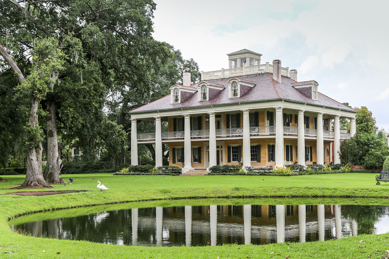 large home with columns and wrap around deck in front of a small pond