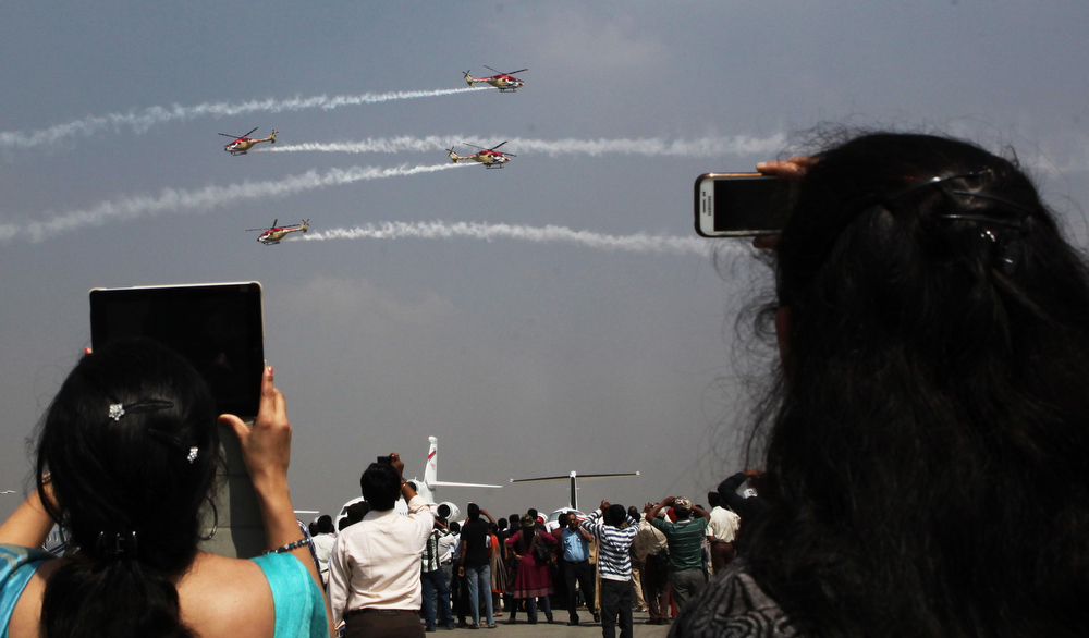 . Visitors look the Indian Air Force Sarang aerobatics team perform during the second day of the ongoing 9th Edition of Aero India Show 2013 in Bangalore on February 7, 2013. India, the world\'s leading importer of weaponry, is hosting one of Asia\'s biggest aviation trade shows with Western suppliers eyeing lucrative deals and a Chinese delegation attending for the first time. AFP PHOTO/ STRSTR/AFP/Getty Images