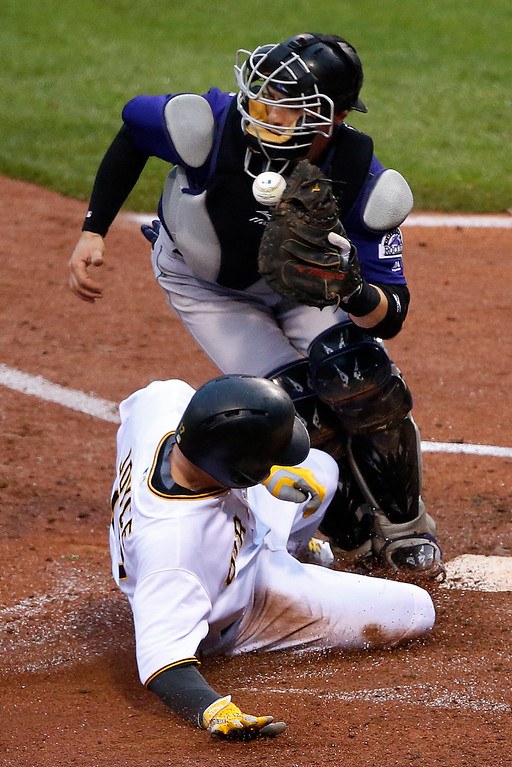 . Pittsburgh Pirates\' Matt Joyce, bottom, scores on a single by Pirates Jordy Mercer when Colorado Rockies catcher Tony Wolters can\'t handle the relay throw from center field during the fourth inning of a baseball game in Pittsburgh, Saturday, May 21, 2016. (AP Photo/Gene J. Puskar)