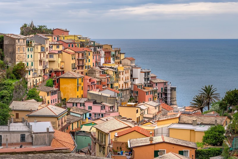Colorful houses on a sloped landscape overlooking the sea on a Cinque Terre hiking trip