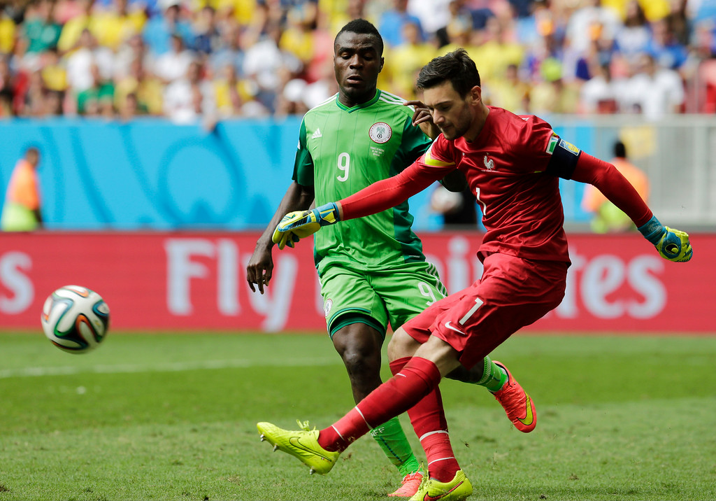 . France\'s goalkeeper Hugo Lloris, right, clears the ball in front of Nigeria\'s Emmanuel Emenike during the World Cup round of 16 soccer match between France and Nigeria at the Estadio Nacional in Brasilia, Brazil, Monday, June 30, 2014. (AP Photo/Petr David Josek)