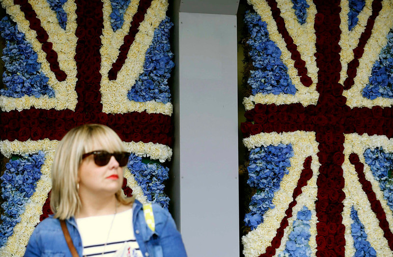 . A woman walks waits in front of two Union flags designed in flowers outside the Floral Design room at the Chelsea Flower Show in London May 21, 2013. REUTERS/Luke MacGregor