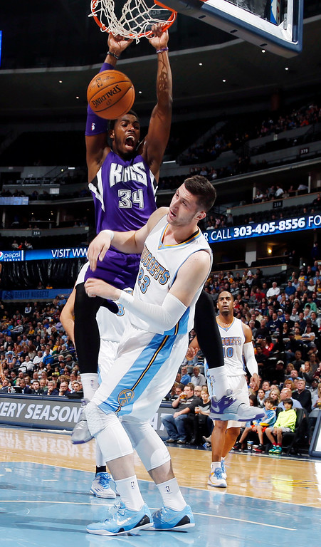 . Sacramento Kings forward Jason Thompson, back, hangs on rim after dunking the ball for a basket over Denver Nuggets center Jusuf Nurkic, of Bosnia Herzegovina, in the first half of an NBA basketball game in Denver on Monday, Nov. 3, 2014. (AP Photo/David Zalubowski)