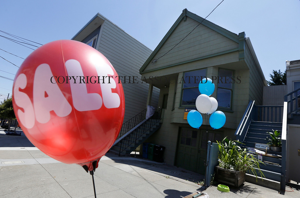 . A sale balloon for a nearby store is shown next to a property in the Noe Valley neighborhood just sold for $1.8 million in cash, $600,000 more than its asking price, in San Francisco, Wednesday, July 30, 2014. In the souped-up world of San Francisco real estate, where the median selling price for homes and condominiums hit seven figures for the first time last month, the cool million that would fetch a mansion on a few acres elsewhere will now barely cover the cost of an 800-square-foot starter home. (AP Photo/Jeff Chiu)