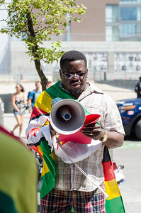 KITCHENER, Ont. (23/07/2016) - Moses Dzimba prepares for a speech during a march concerning Zimbabwe government.  Members of the Zimbabwe Canada Association of Waterloo, gather together at Victoria Park for a peaceful march to draw attention to government and human rights violations in Zimbabwe. There has been a civic unrest across the country without response from the government. #thisflag is the hash tag created by Pastor Evan Mawarire to begin a boycott earlier this month to bring awareness to what in happening in Zimbabwe.  Rev. James Kandoje, President of the association led the march from Victoria Park to Kitchener City Hall via Jacob, Queen, and King St.  Photos by Alicia Wynter/The Record