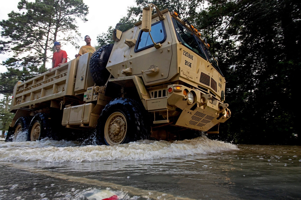 . The Louisiana National Guard transports people out of flood hit areas around Walker , La., Monday, Aug. 15, 2016. Although some flood waters have receded roads continue to be difficult to pass with private vehicles. (AP Photo/Max Becherer)