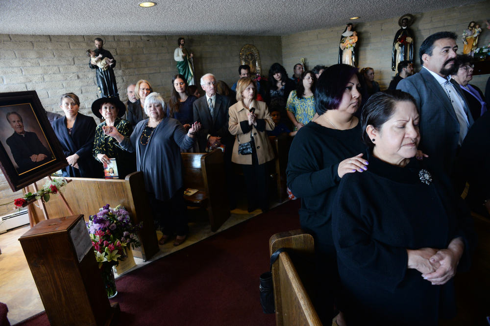 . Mourners pray during the packed funeral for Father Tomas Fraile at St. Cajetan Church at 299 South Raleigh St. in Denver, Co on March 26, 2014.  Hundreds of people turned out to pay their last respects for the popular father.  (Photo By Helen H. Richardson/ The Denver Post)