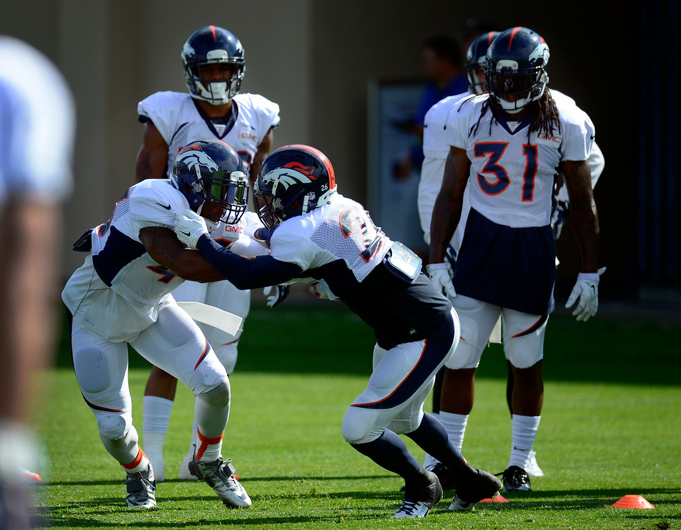 . Members of the defense run through drills on Saturday. The Denver Broncos football team hold their workouts for the team during mini-camp at Dove Valley in Centennial on Saturday, July 26, 2014. (Photo by Kathryn Scott Osler/The Denver Post)
