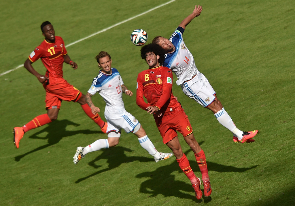 . Belgium\'s midfielder Marouane Fellaini (2R) and Russia\'s defender Vasily Berezutsky (R) challenge for the ball as Russia\'s defender Andrei Yeshchenko (2L) and Belgium\'s forward Divock Origi (L) look on during the Group H football match between Belgium and Russia at The Maracana Stadium in Rio de Janeiro on June 22, 2014, during the 2014 FIFA World Cup. AFP PHOTO / YASUYOSHI CHIBA