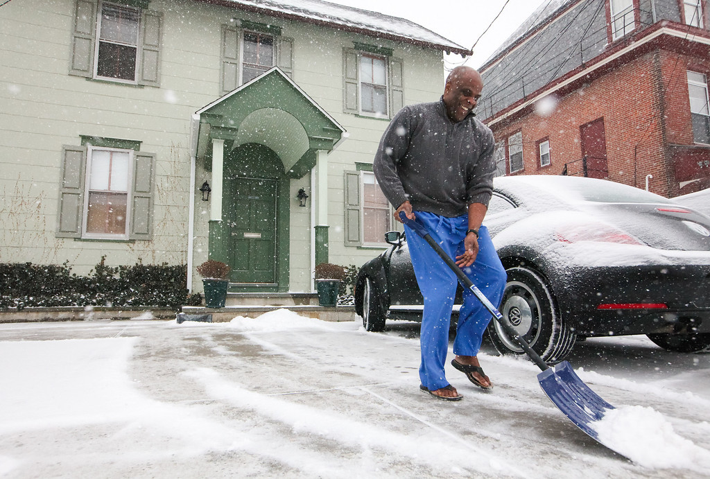 . Neal Hall clears his parking area of snow in Hockessin, Del., Tuesday, Jan. 21, 2014. (AP Photo/The Wilmington News-Journal, Suchat Pederson)