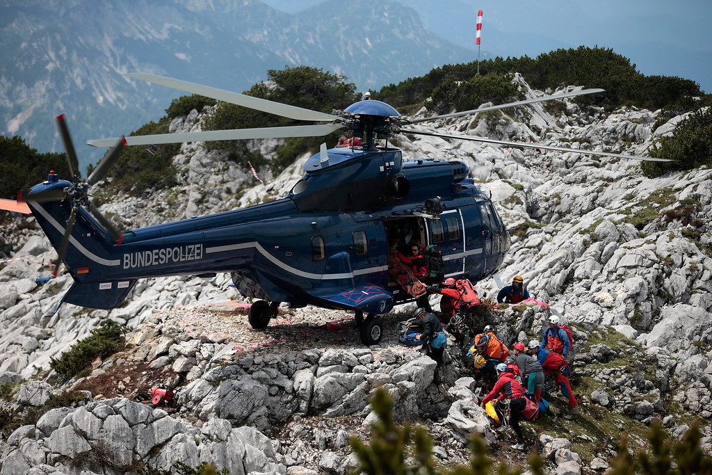 . Rescue workers transport equipment into a police helicopter near the entrance to the Riesending vertical cave after the final phase of the transport of injured spelunker Johann Westhauser to the surface on June 19, 2014 near Marktschellenberg, Germany.   (Photo by Johannes Simon/Getty Images)