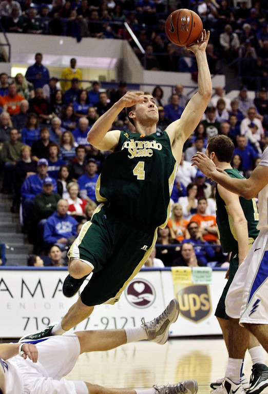 . Colorado State\'s Pierce Hornung (4) shoots while leaping over downed Air Force player Marek Olesinski, bottom, during the second half of an NCAA college basketball game in Air Force Academy, Colo., Saturday, Feb. 16, 2013. Colorado State won 89-86. (AP Photo/Brennan Linsley)