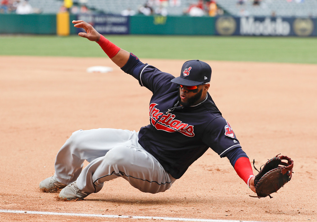 . Cleveland Indians first baseman Carlos Santana fields a ball hit down the first base line by Los Angeles Angels\' Kole Calhoun during the fourth inning of a baseball game in Anaheim, Calif., Thursday, Sept. 21, 2017. Calhoun was out at first. (AP Photo/Chris Carlson)