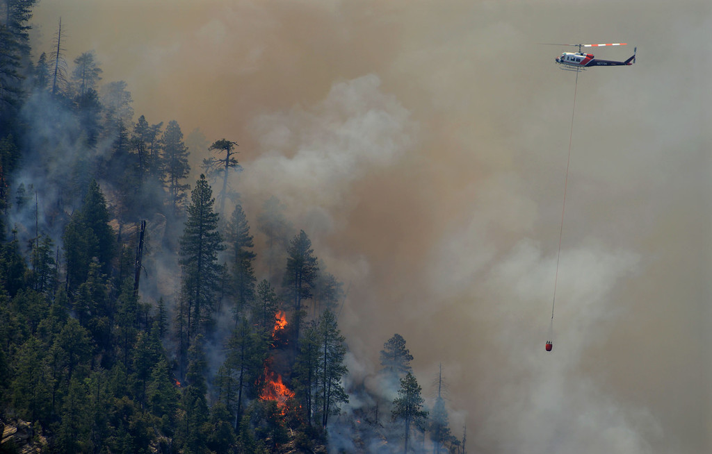 . A firefighting helicopter drops water on a forest fire in Oak Creak Canyon in Sedona, Az., on Thursday May 22, 2014. The human-caused Slide Fire started Tuesday and had burned 7 1/2 square miles in and around Oak Creek Canyon, a scenic recreation area along a highway between Sedona and Flagstaff that normally would be teeming with tourists as the Memorial Day weekend approaches. (AP Photo/ Vyto Starinskas)