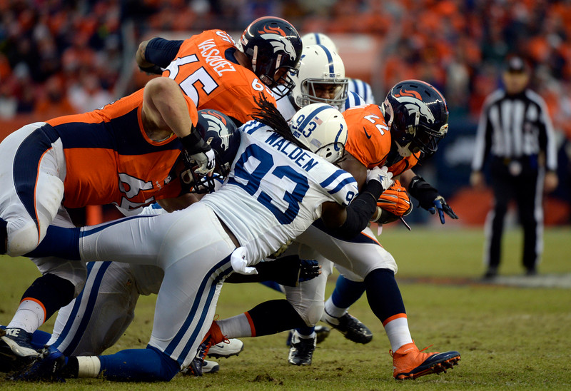 . C.J. Anderson (22) of the Denver Broncos gets wrapped up and taken down in the first half.  The Denver Broncos played the Indianapolis Colts in an AFC divisional playoff game at Sports Authority Field at Mile High in Denver on January 11, 2015. (Photo by Brent Lewis/The Denver Post)