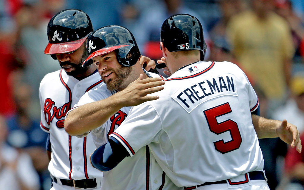 . Atlanta\'s Evan Gattis, center, is embraced by teammate Freddie Freeman, right, after hitting a grand slam to score Freeman, Jason Heyward, left, and Ramiro Pena, not pictured, in the fourth inning against the Twins at Turner Field in Atlanta on Wednesday, May 22, 2013.  Gattis\' home run was the big blow in the Twins\' 8-3 loss. (AP Photo/David Goldman)