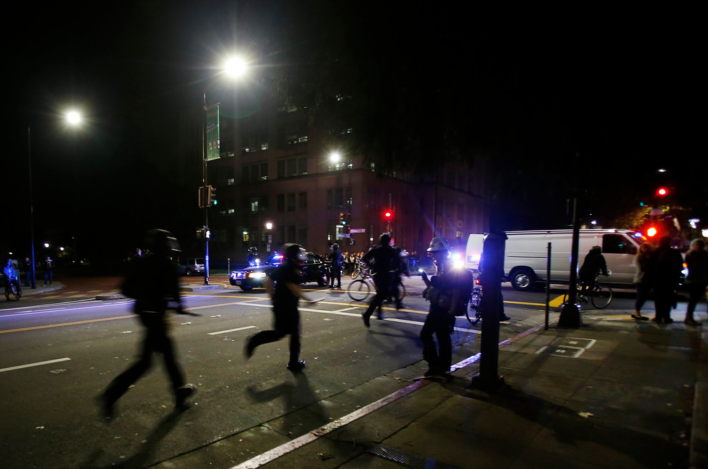 . Police officers run down Milvia Street in Berkeley, Calif., late Sunday evening, Dec. 7, 2014, after protesters vandalized the front doors of the Martin Luther King Jr. Civic Center building during a second consecutive night of unrest in the city over the killings of two unarmed black men by police in Ferguson, Mo., and New York. (Karl Mondon/Bay Area News Group)