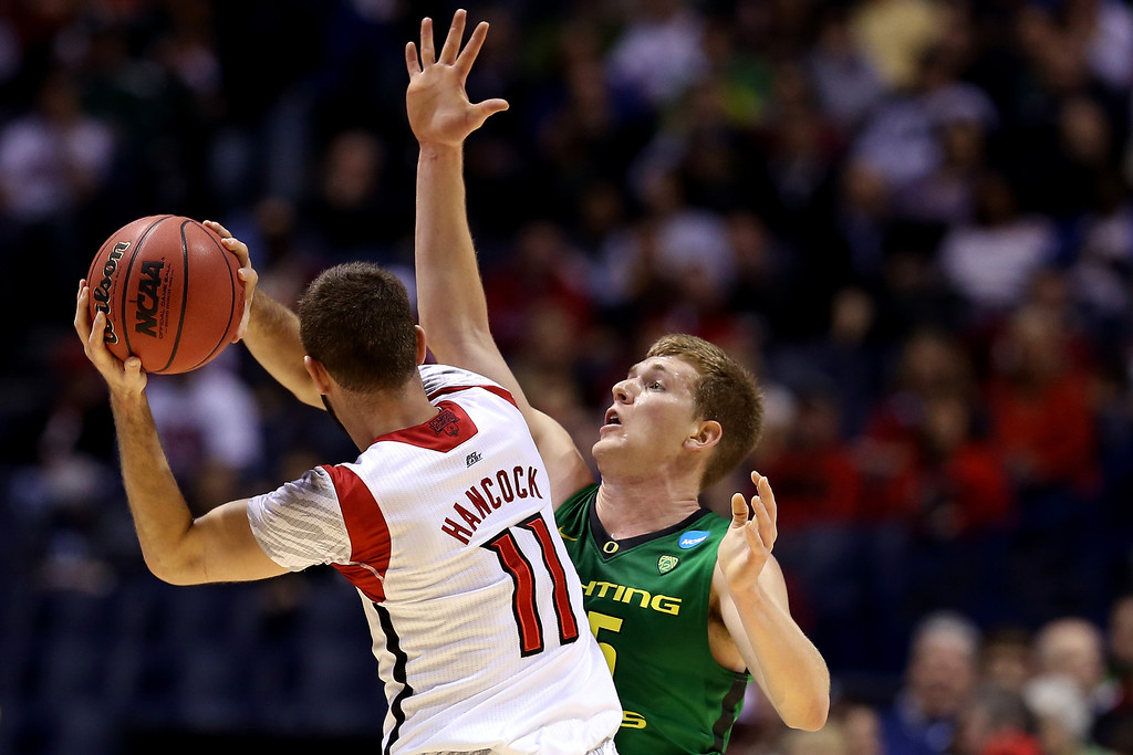 . E.J. Singler #25 of the Oregon Ducks defends in the first half against Luke Hancock #11 of the Louisville Cardinals during the Midwest Region Semifinal round of the 2013 NCAA Men\'s Basketball Tournament at Lucas Oil Stadium on March 29, 2013 in Indianapolis, Indiana.  (Photo by Streeter Lecka/Getty Images)