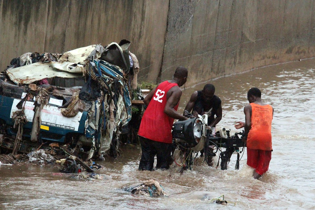 . People try to remove valuables submerged in a flooded street after at least 90 people were killed in a petrol station fire in Ghana\'s capital, Accra, on June 4, 2015. The fire broke out at the filling station in the Kwame Nkrumah Circle area of the city late on Wednesday night and is thought to have spread from a nearby residence. AFP PHOTO / FATI BRAIMAH/AFP/Getty Images