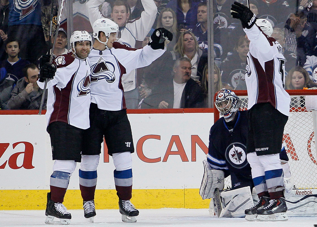 . Colorado Avalanche\'s Maxime Talbot (25), Nick Holden (2) and Cody McLeod (55) celebrate Holden\'s goal against Winnipeg Jets goaltender Al Montoya during the second period of an NHL hockey game Wednesday, March 19, 2014, in Winnipeg, Manitoba. (AP Photo/The Canadian Press, John Woods)