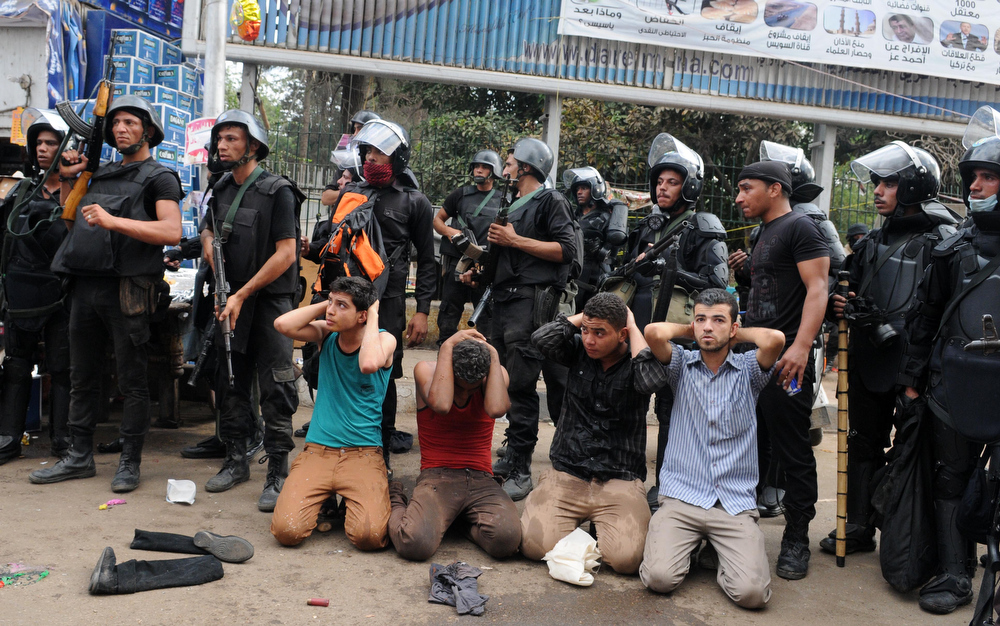 . Egyptian security forces detain supporters of ousted Islamist President Mohammed Morsi as they clear a sit-in camp set up near Cairo University in Cairo\'s Giza district, Egypt, Wednesday, Aug. 14, 2013. Egyptian police in riot gear swept in with armored vehicles and bulldozers Wednesday to clear the sit-in camp and the other set up by supporters of the country\'s ousted Islamist president in Cairo, showering protesters with tear gas as the sound of gunfire rang out. (AP Photo/Mohammed Asad)