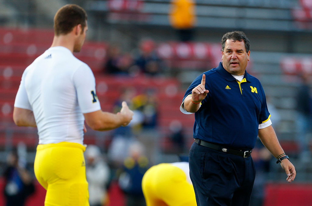 . Michigan coach Brady Hoke walks among his players as they prepare for an NCAA college football game against Rutgers on Saturday, Oct. 4, 2014, in Piscataway, N.J. (AP Photo/Rich Schultz)