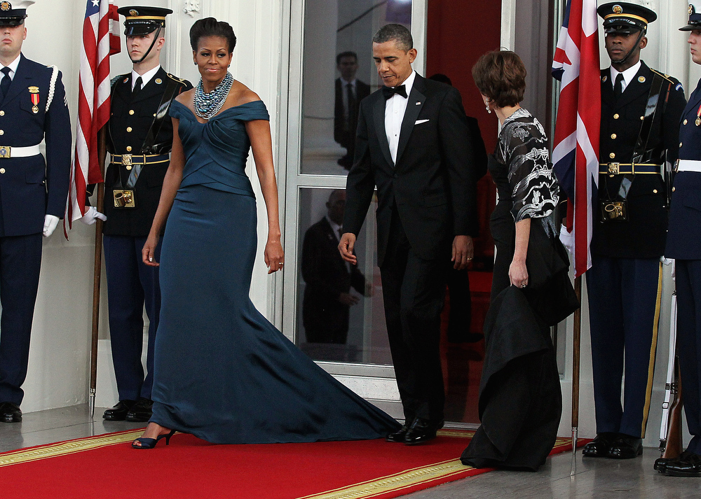 Description of . U.S. President Barack Obama (C) accidentially steps on First lady Michelle Obama's dress as they walk onto the North Portico before the arrival of British Prime Minister David Cameron and his wife Samantha Cameron the White House March 14, 2012 in Washington, DC. Cameron is on a three-day visit to the U.S. and he was expected to have talks with Obama on the situations in Afghanistan, Syria and Iran.  (Photo by Alex Wong/Getty Images)