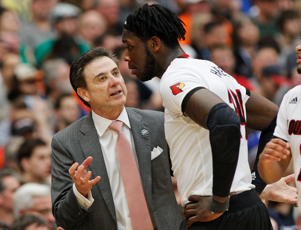 . Louisville head coach Rick Pitino, left, talks to Louisville\'s Montrezl Harrell during the second half of a regional final against Michigan State in the NCAA men\'s college basketball tournament Sunday, March 29, 2015, in Syracuse, N.Y. (AP Photo/Nick Lisi)
