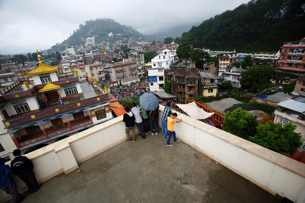 . Tibetan youths observe celebrations of the 78th birthday of exiled spiritual leader Dalai Lama from the roof of a monastery in Kathmandu July 6, 2013. During last month\'s visit of Chinese State Councilor Yang Jiechi, Chairman of the Interim Election Council Khil Raj Regmi said Nepal is firmly committed to the One-China Policy and reaffirmed its stand that the territory of Nepal will not be allowed to be used for any activities against China. Nepal ceased issuing refugee papers to Tibetans in 1989 and recognizes Tibet to be a part of China. REUTERS/Navesh Chitrakar